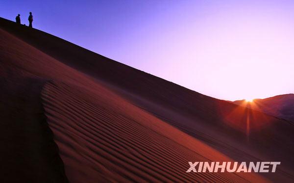 Para pelancong ini kelihatan sedang berada di puncak bukit pasir yang